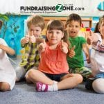 Group of kids sitting on the floor giving us a thumbs up for our best daycare fundraiaisng ideas 1