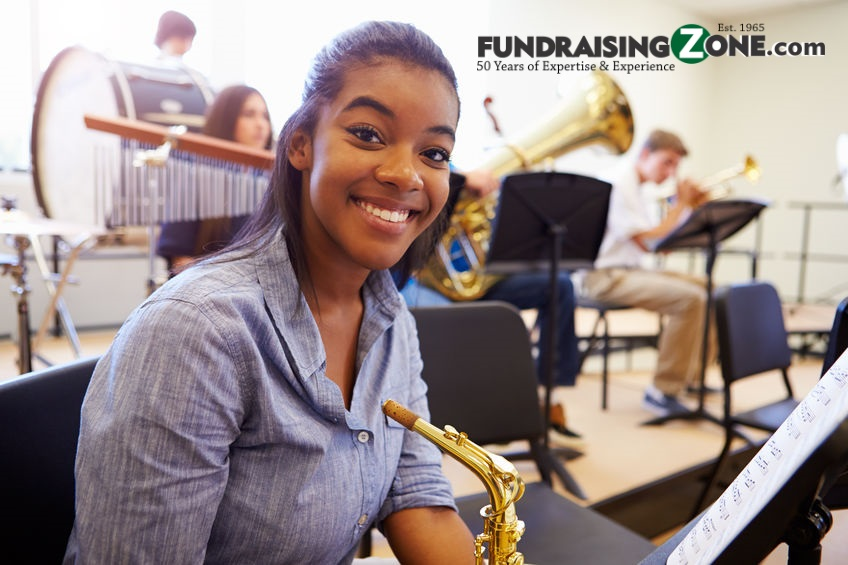 Girl with saxophone smiles thinking about how easy these band fundraisers are.